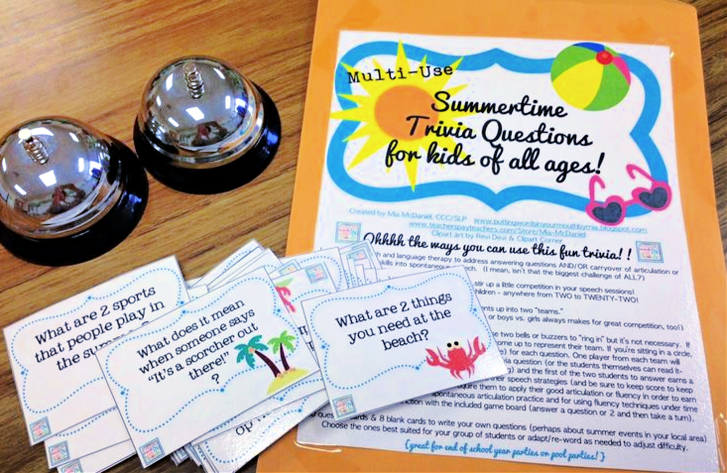 """a photo of summer question cards, 2 service bells and a manilla envelope on a table. The folder is labeled """"Summertime trivia questions for kids of all ages."""""""